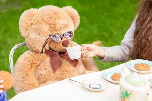 Śliczna dziewczyna daje herbatę pluszowemu misiowi na podwórku