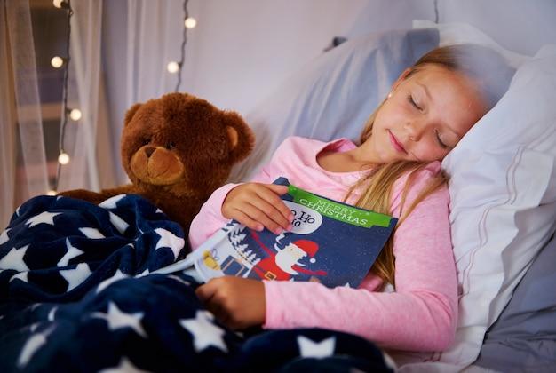 Śliczna dziewczyna drzemie z książką