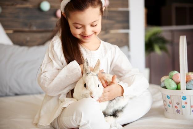 Śliczna dziewczyna głaszcząca puszystego królika w łóżku