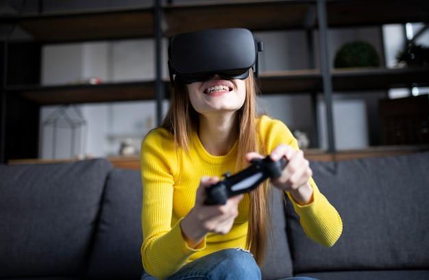 Śliczna dziewczyna gra na konsoli. szczęśliwa młoda kobieta za pomocą zestawu słuchawkowego wirtualnej rzeczywistości
