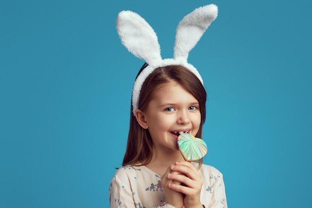 Śliczna dziewczyna gryzie ciasteczko w kształcie serca, ubrana w uszy królika na niebieskiej ścianie