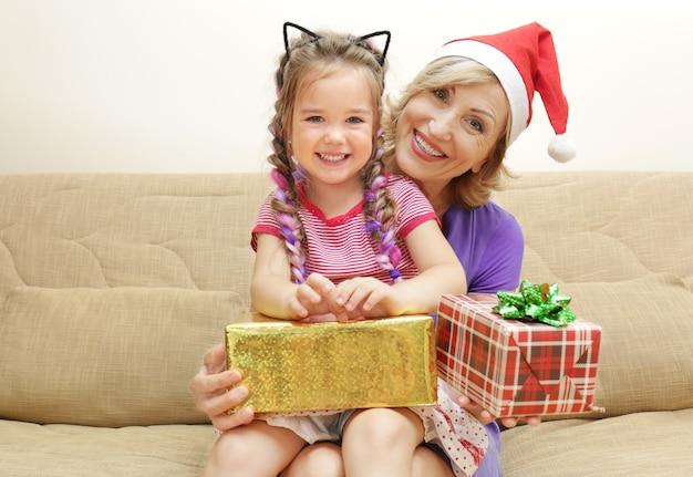 Śliczna dziewczyna i babcia z świątecznymi prezentami na kanapie w domu