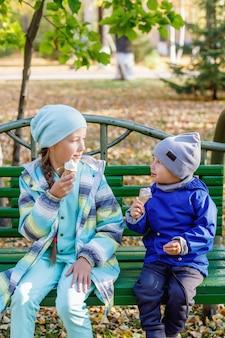 Śliczna dziewczyna i chłopak, siostra i brat jedzą lody w jesiennym parku