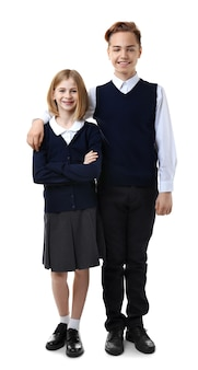 Śliczna dziewczyna i chłopak w szkolnym mundurku na białym tle