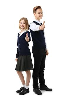 Śliczna dziewczyna i chłopak w szkolnym mundurku pokazując kciuk do góry gest na białym tle