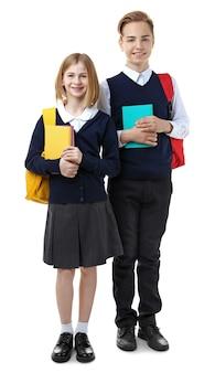 Śliczna dziewczyna i chłopak w szkolnym mundurku trzyma książki na białym tle