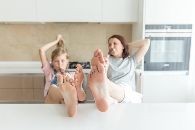 Śliczna dziewczyna i jej matka są uśmiechnięci podczas gdy jedzący lody w kuchni z nogami na stole
