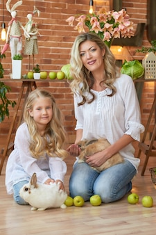 Śliczna dziewczyna i matka bawić się z królikami