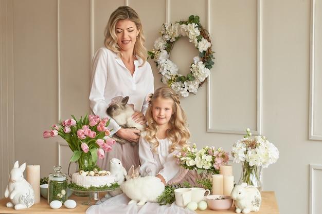 Śliczna dziewczyna i matka bawić się z królikiem w dekorującym pokoju