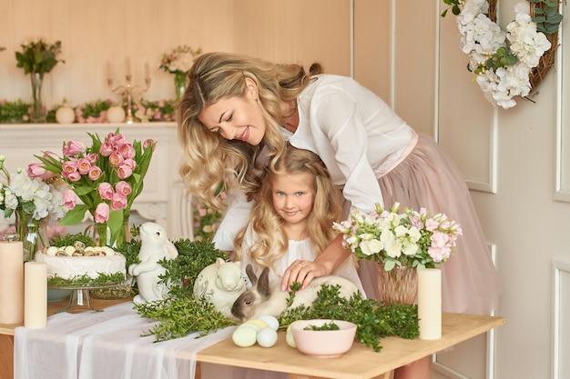 Śliczna dziewczyna i matka bawić się z królikiem