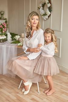 Śliczna dziewczyna i matka w dekorującym pokoju z kwiatami