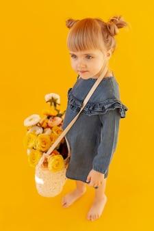 Śliczna dziewczyna jest ubranym kwiatu kosz