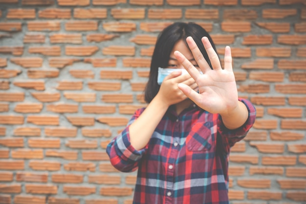 Śliczna dziewczyna jest ubranym maskę i robi stop ręce od innej prople onb rick ściany ściany