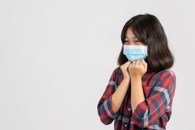 Śliczna dziewczyna jest ubranym maskę podczas gdy szybujący gardło na biel ścianie.