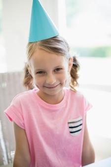 Śliczna dziewczyna jest ubranym partyjnego kapelusz w domu