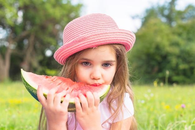 Śliczna dziewczyna jest ubranym różowego kapeluszowego łasowanie arbuza plasterek w parku
