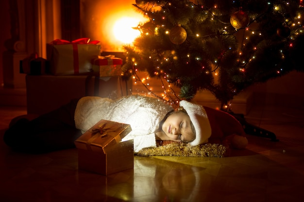 Śliczna dziewczyna leżąca pod choinką i patrząca w świecące pudełko na prezent