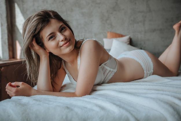 Śliczna dziewczyna leżąca rano na łóżku w białej pościeli