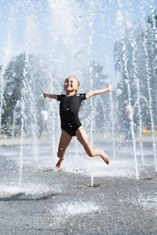 Śliczna dziewczyna ma zabawę przy fontanną