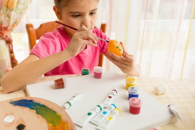 Śliczna dziewczyna malująca kolorowe jajka na wielkanoc