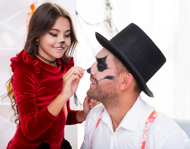 Śliczna dziewczyna maluje ojciec twarz na halloween