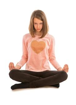 Śliczna dziewczyna medytuje siedząc w pozycji lotosu na białym tle