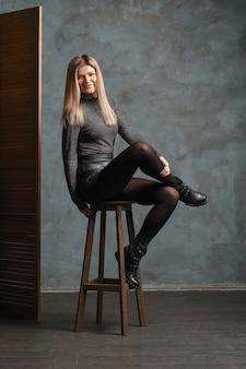 Śliczna dziewczyna na górze, skórzane szorty i gęste rajstopy siedzące na krześle