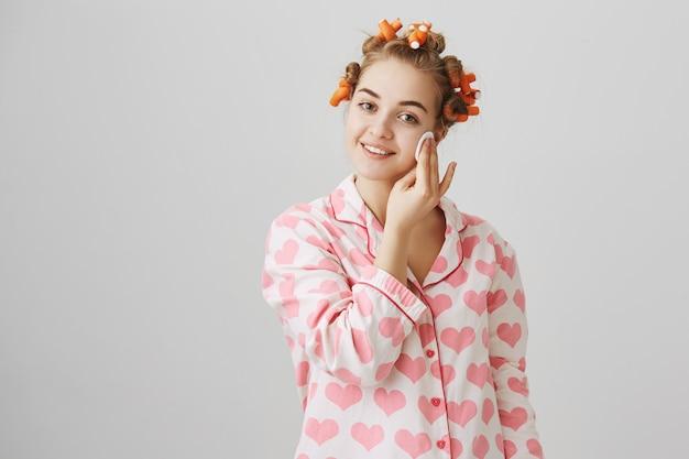 Śliczna dziewczyna nałóż środek czyszczący przed snem za pomocą wacika, ubrana w lokówki i piżamę