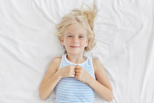 Śliczna dziewczyna o blond włosach, niebieskich czarujących oczach i piegowatej twarzy, ubrana w marynarski t-shirt, leżąca na białym narzucie, z radosnym wyrazem twarzy po nocnych snach. dzieci, relaks