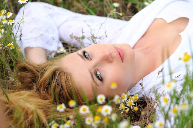 Śliczna dziewczyna o jasnozielonych oczach leży na trawie i kwiatach. portret kobiety z rękami na głowie