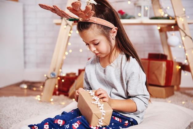 Śliczna dziewczyna otwiera prezent gwiazdkowy