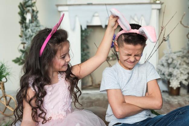 Śliczna dziewczyna patrzeje obrażającej chłopiec w królików ucho