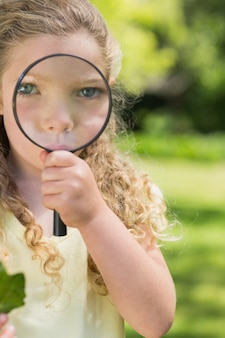Śliczna dziewczyna patrzeje przez powiększać - szkło przy parkiem