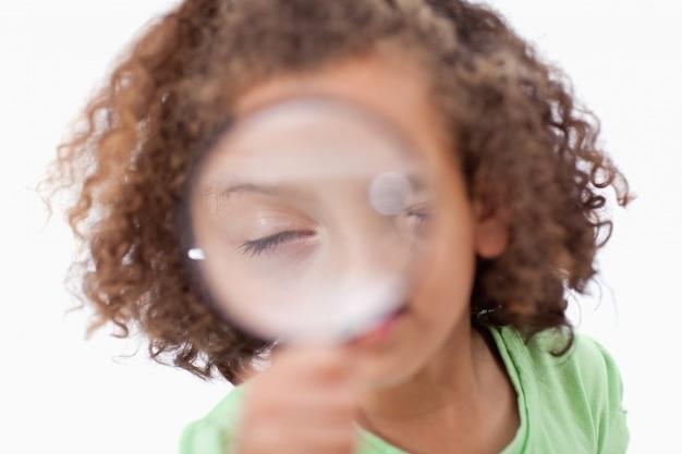 Śliczna dziewczyna patrzeje przez powiększać - szkło