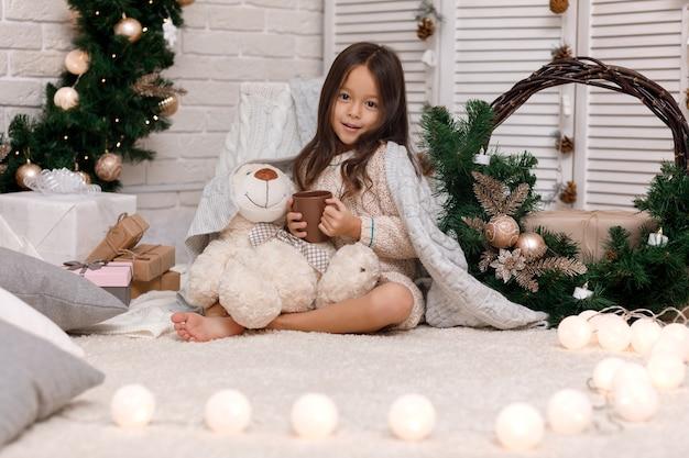 Śliczna dziewczyna pije gorącą czekoladę i bawi się w domu z misiem na boże narodzenie