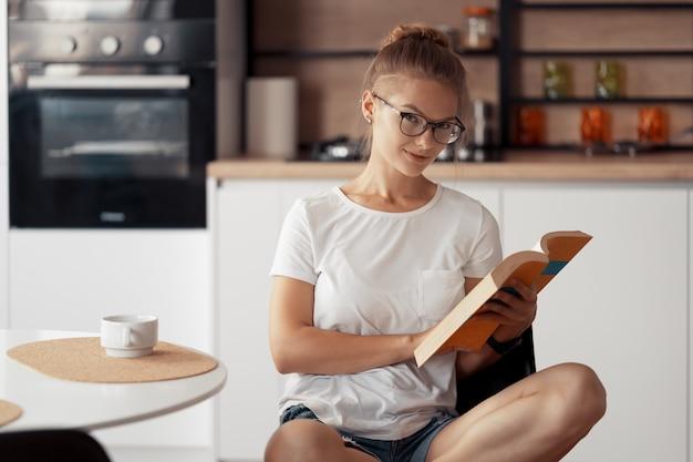 Śliczna dziewczyna pije kawę i czyta książkę przy kuchennym stole w domu