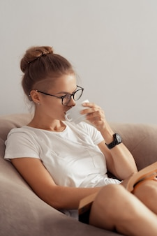 Śliczna dziewczyna pije kawę i czyta książkę w domu
