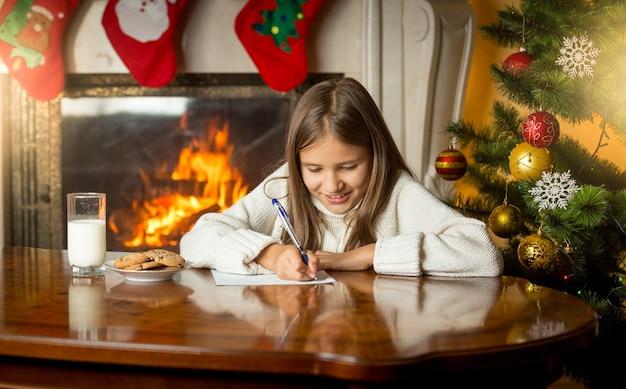 Śliczna dziewczyna pisze list do świętego mikołaja w wigilię bożego narodzenia