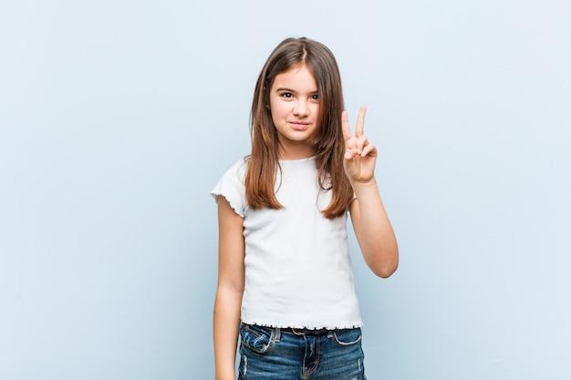 Śliczna dziewczyna pokazuje numer dwa z palcami.