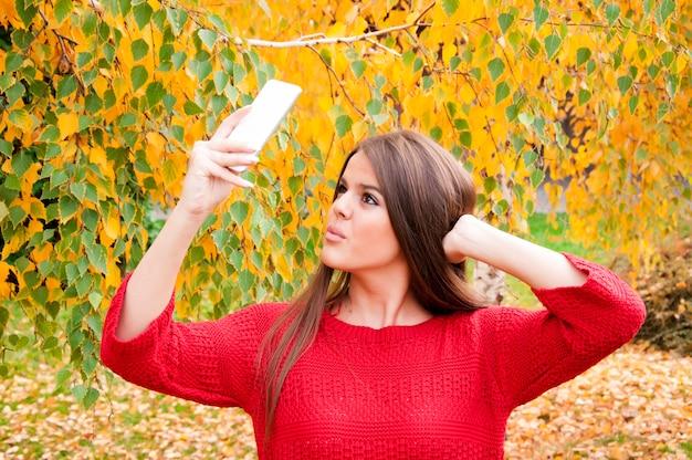 Śliczna dziewczyna pozuje dla selfie wśród natury