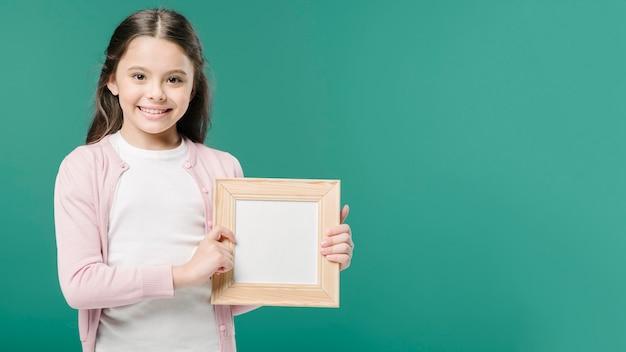 Śliczna dziewczyna pozuje z fotografii ramą w studiu