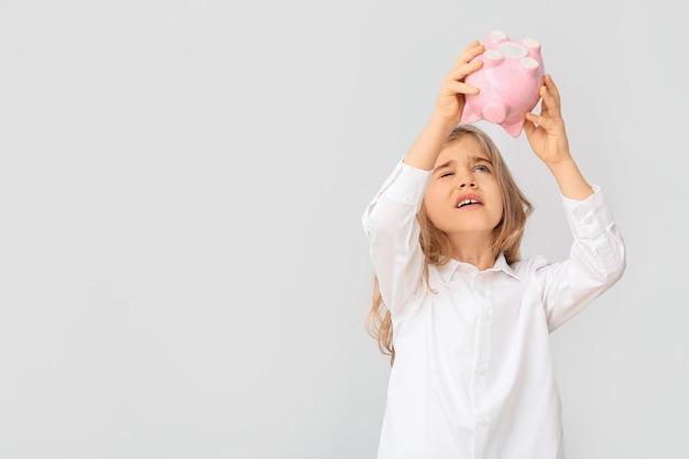Śliczna dziewczyna przechyla pieniądze ze skarbonki na biały