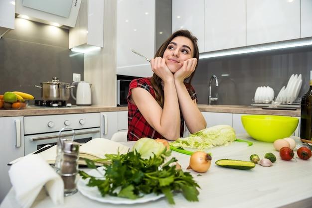 Śliczna dziewczyna przygotowuje sałatkę z różnych warzyw i zieleni dla zdrowego stylu życia
