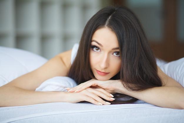 Śliczna dziewczyna rano na białym łóżku