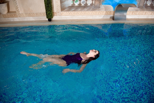 Śliczna dziewczyna relaksuje się w basenie. relaks przy basenie.