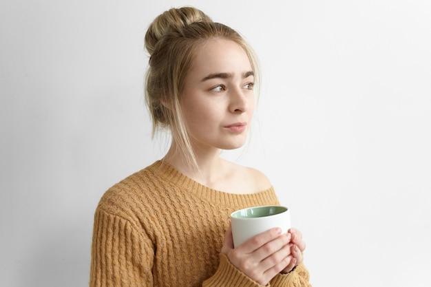 Śliczna dziewczyna rozgrzewa się po studiach, pije gorącą czekoladę z dużego kubka. atrakcyjna młoda kobieta czuje się przytulnie przy herbacie lub kawie, trzymając kubek, ubrana w stary przytulny sweter oversize