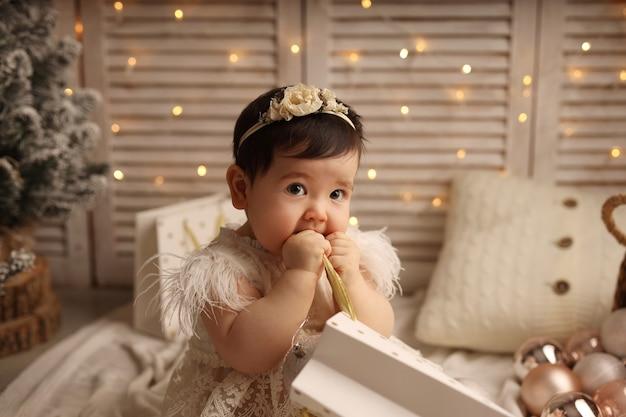 Śliczna dziewczyna siedzi na dzianinowym kocu i bawi się paczką prezentów na nowy rok