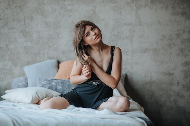 Śliczna dziewczyna siedzi na łóżku rano w czarnej bieliźnie