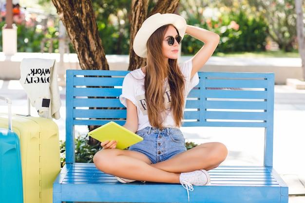 Śliczna dziewczyna siedzi na niebieskiej ławce i gra na tablecie w żółtym etui.