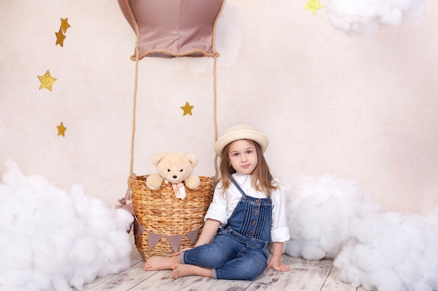 Śliczna dziewczyna siedzi na ścianie balon, gwiazdy i chmury i trzyma misia. mała dziewczynka marzy. dziewczynka bawi się zabawką w pokoju dziecięcym. wystrój pokoju dziecięcego. zabawki dla niemowląt i pluszowe